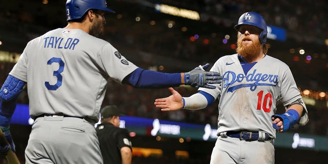 Los Angeles Dodgers' Justin Turner, right, is congratulated by Chris Taylor after scoring against the San Francisco Giants during the ninth inning of Game 5 of a baseball National League Division Series Thursday, Oct. 14, 2021, in San Francisco.