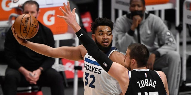 Karl-Anthony Towns (32) of the Minnesota Timberwolves looks to pass the ball as he is defended by Ivica Zubac (40) of the Los Angeles Clippers during the first half of a game at Staples Center April 18, 2021 in Los Angeles, California.