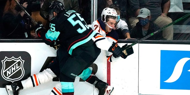 Seattle Kraken's Jeremy Lauzon (55) collides with Edmonton Oilers' Ryan McLeod in the third period of a preseason NHL hockey game Friday, Oct. 1, 2021, in Everett, Wash.