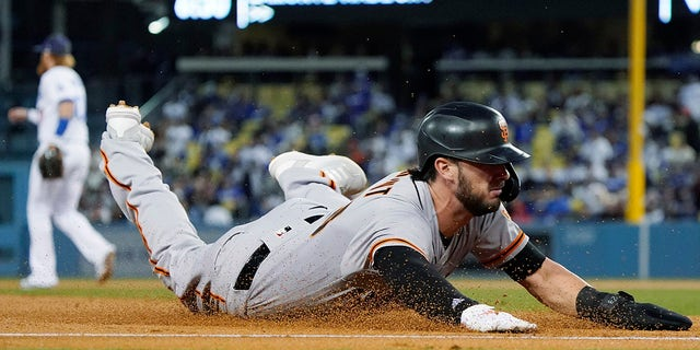 The San Francisco Giants' Kris Bryant slides safely into third base on a single by LaMonte Wade Jr. during the second inning of Game 4 of a baseball National League Division Series against the Los Angeles Dodgers, Tuesday, Oct. 12, 2021, in Los Angeles.