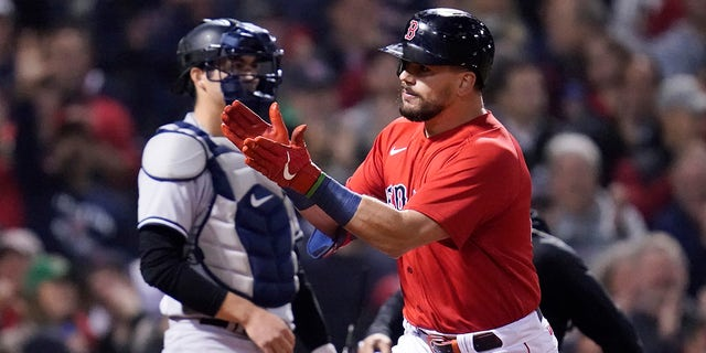 Boston Red Sox's Kyle Schwarber celebrates his solo homer in front of New York Yankees catcher Kyle Higashioka in the third inning of an American League Wild Card playoff baseball game against the New York Yankees at Fenway Park, Tuesday, Oct. 5, 2021, in Boston.