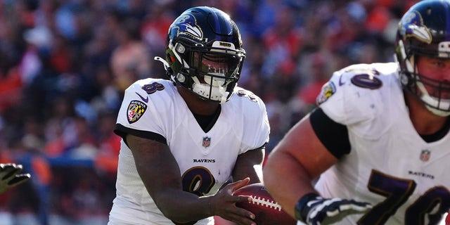 Oct 3, 2021; Denver, Colorado, USA; Baltimore Ravens quarterback Lamar Jackson (8) takes a hike in the second quarter against the Denver Broncos at Empower Field at Mile High.