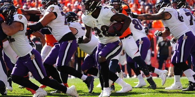 Oct 3, 2021; Denver, Colorado, USA; Baltimore Ravens running back Latavius Murray (28) carries the ball in the first quarter against the Denver Broncos at Empower Field at Mile High.