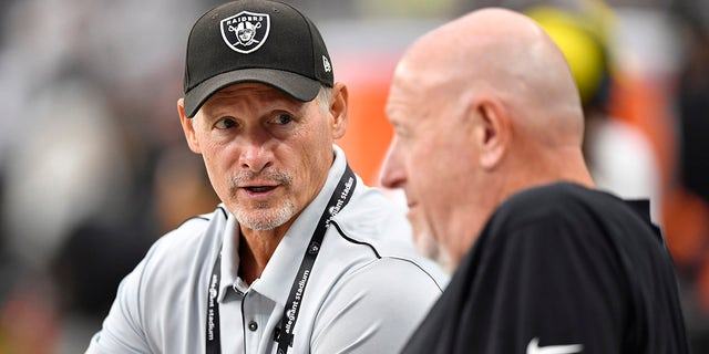 General manager Mike Mayock of the Las Vegas Raiders speaks to offensive line coach Tom Cable before a preseason game against the Seattle Seahawks at Allegiant Stadium on August 14, 2021 in Las Vegas, Nevada. The Raiders defeated the Seahawks 20-7.