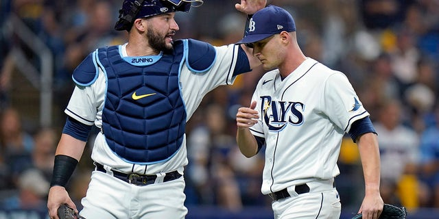 Tampa Bay Rays catcher Mike Zunino, left, gives starting pitcher Shane McClanahan a pat on the head after the top of the second inning against the Boston Red Sox in Game 1 of a baseball American League Division Series on Thursday, Oct. 7, 2021, in St. Petersburg, Fla.