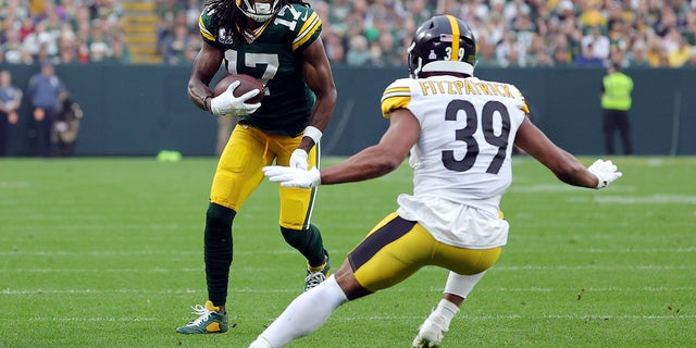 Davante Adams (17) of the Green Bay Packers catches the ball and is tackled by Minkah Fitzpatrick (39) of the Pittsburgh Steelers during the second quarter at Lambeau Field on Oct. 03, 2021 in Green Bay, Wisconsin.