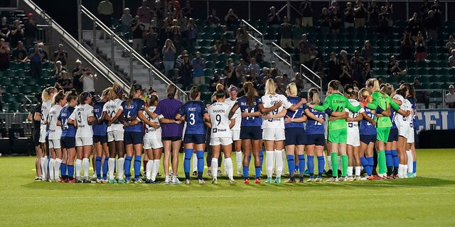 North Carolina Courage and Racing Louisville FC players pause and gather at midfield during the first half of an NWSL soccer match in Cary, N.C., Wednesday, Oct. 6, 2021.