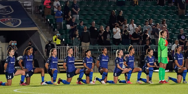 North Carolina Courage players take a knee during the national anthem prior to the team's NWSL soccer match against Racing Louisville FC in Cary, N.C., Wednesday, Oct. 6, 2021.