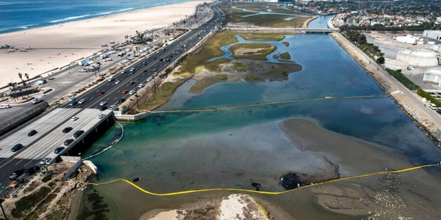 An aerial photo shows floating barriers known as booms to try to stop further incursion into the Wetlands Talbert Marsh after an oil spill in Huntington Beach, Calif., on Huntington Beach, Calif., on Monday, Oct. 4, 2021.