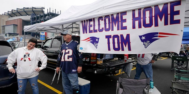 New England Patriots fan Stephanie Lamontagne, left, of Merrimack, N.H. smiles while chatting with Bill Gately, of Burrillville, R.I., while tailgating near a sign greeting the return of quarterback Tom Brady prior to an NFL football game between the New England Patriots and Tampa Bay Buccaneers, Sunday, Oct. 3, 2021, in Foxborough, Mass.