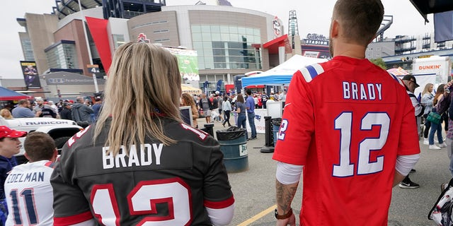 Melissa Zaske, left, of Vancouver, wears Tom Brady's Tampa Bay Buccaneers jersey while walking with her husband Derek, who wears Tom Brady's old New England Patriots jersey, prior to a game between the New England Patriots and Tampa Bay Buccaneers, Sunday, Oct. 3, 2021, in Foxborough, Mass.