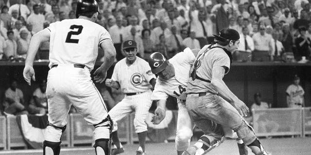 In this July 14, 1970, file photo, the National League's Pete Rose slams into American League catcher Ray Fosse to score the winning run during the 12th inning of the baseball All-Star Game in Cincinnati. Looking on are third base coach Leo Durocher and on-deck batter Dick Dietz (2).