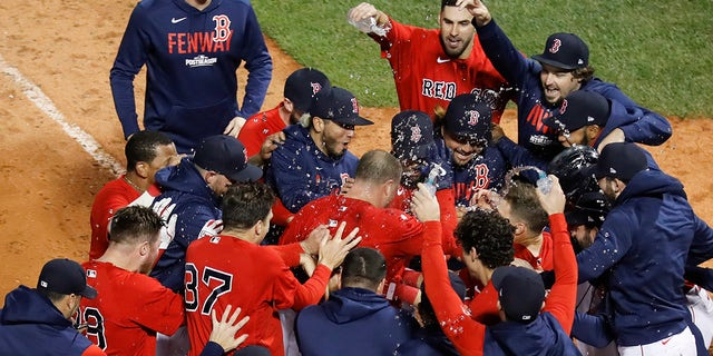 Boston Red Sox Christian Vazquez is mobbed by teammates after hitting a two-run walk-off home run during the thirteenth inning against the Tampa Bay Rays during Game 3 of a baseball American League Division Series, Sunday, Oct. 10, 2021, in Boston. Boston won 6-4.