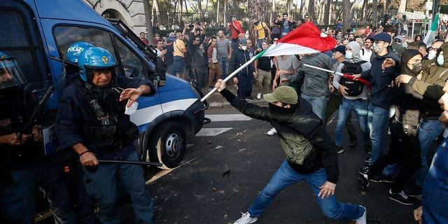 Affrontements entre policiers et manifestants lors d'une manifestation à Rome, samedi 9 octobre 2021. Des milliers de manifestants ont manifesté samedi à Rome contre la carte sanitaire COVID-19 que les travailleurs italiens, publics et privés, doivent exhiber pour se rendre sur leur lieu de travail.  A partir du 15 octobre par arrêté gouvernemental.