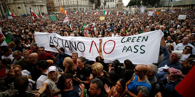 People gather in Piazza del Popolo square during a protest, in Rome, Saturday, Oct. 9, 2021. Thousands of demonstrators protested Saturday in Rome against the COVID-19 health pass that Italian workers, both the public and private sectors, must display to access their workplaces from Oct. 15 under a government decree.