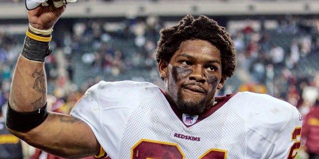 امنیت واشنگتن ردسکینز شان تیلور دست خود را برای قدردانی از طرفداران بالا می برد پس از آنکه قرمزها در این عکس 1 ژانویه 2006 در فیلادلفیا عقاب فیلادلفیا را در فیلادلفیا شکست دادند.  تیلور که در 26 نوامبر 2007 در محل اقامت خود در فلوریدا مورد اصابت گلوله قرار گرفت و کشته شد ، پس از مرگ در 18 دسامبر 2007 به عنوان تازه کار NFL Pro Bowl انتخاب شد.
