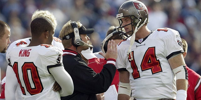 Quarterback Brad Johnson (14) of the Tampa Bay Buccaneers talks to his head coach Jon Gruden during the game against the Tennessee Titans on Dec. 28, 2003, at The Coliseum in Nashville, Tennessee. The Titans defeated the Buccaneers, 33-13. Quarterback Shaun King (10) is at left.