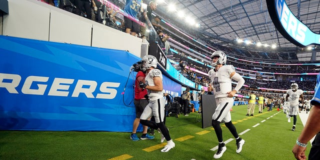 Las Vegas Raiders quarterback Derek Carr (4) and other players leave the field due to a weather delay shortly before the scheduled start an NFL football game against the Los Angeles Chargers, Monday, Oct. 4, 2021, in Inglewood, Calif.