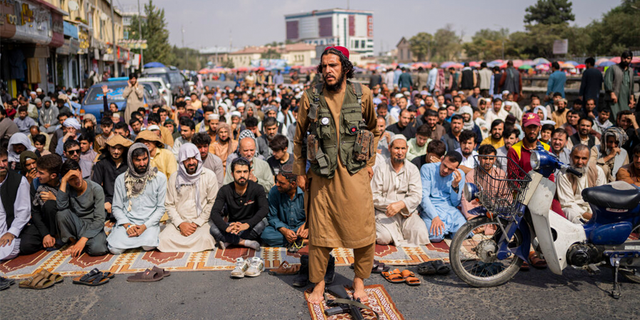 A Taliban fighter, foreground, and a group of Afghan men attend Friday prayers in Kabul, Afghanistan, Friday, Sept. 24, 2021.
