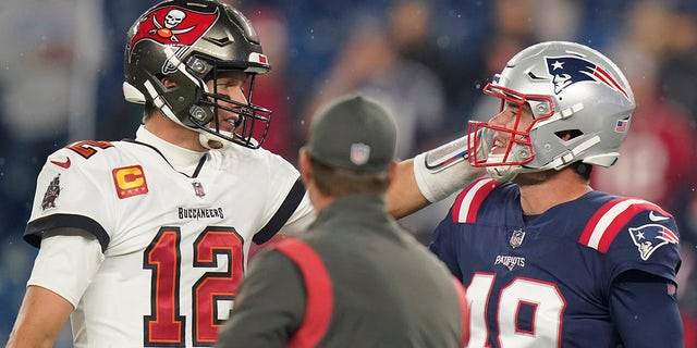 Tampa Bay Buccaneers quarterback Tom Brady (12) meets with New England Patriots long snapper Joe Cardona (49) before a game between the New England Patriots and Tampa Bay Buccaneers, Sunday, Oct. 3, 2021, in Foxborough, Mass.
