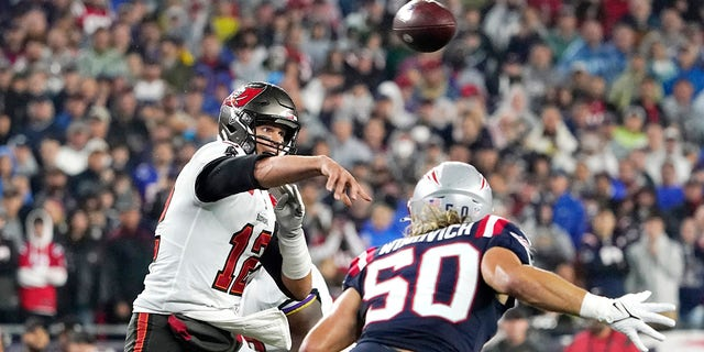Tampa Bay Buccaneers quarterback Tom Brady (12) throws a pass while pressured by New England Patriots defensive end Chase Winovich (50) during the first half of an NFL football game, Sunday, Oct. 3, 2021, in Foxborough, Mass.