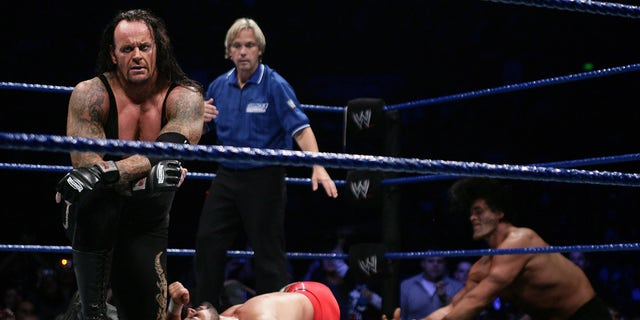 The Undertaker (L) celebrates his victory during the WWE Smackdown at Acer Arena June 15, 2008 in Sydney, Australia.