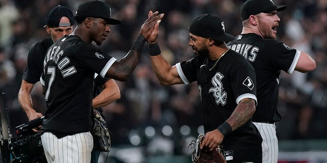 The Chicago White Sox's Tim Anderson (7) and Leury Garcia, center, celebrate with Liam Hendriks, right, after beating the Houston Astros 12-6 in Game 3 of the American League Division Series Sunday, Oct. 10, 2021, in Chicago.