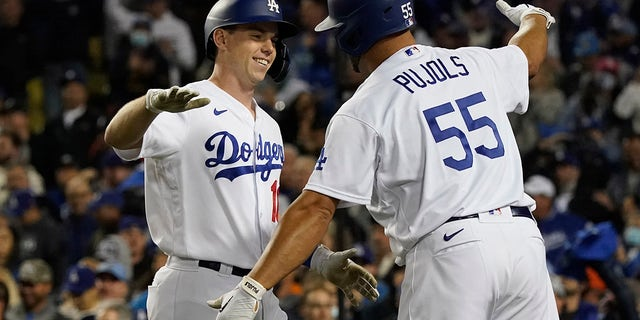 The Los Angeles Dodgers' Will Smith, left, is greeted by Albert Pujols (55) after Smith hit a two-run home run to score Corey Seager during the eighth inning of Game 4 of the National League Division Series against the San Francisco Giants, Tuesday, Oct. 12, 2021, in Los Angeles. The Dodgers won 7-2.