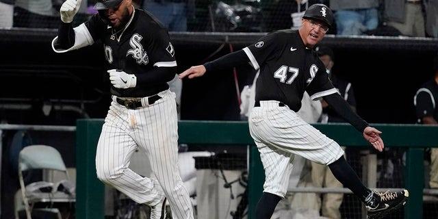Yoán Moncada de los Chicago White Sox, a la izquierda, sábado en Chicago, oct.  2, sábado, Detroit celebra con el entrenador de tercera base Joe McQueen luego de anotar un jonrón de dos carreras durante la octava entrada del juego de béisbol contra los Tigres.