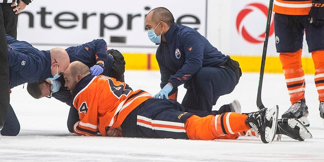 Edmonton Oilers' Zack Kassian (44) is tended to by medical staff after a fight with Vancouver Canucks' Zack MacEwen during the third period of an NHL hockey preseason game Thursday, Oct. 7, 2021, in Edmonton, Alberta.