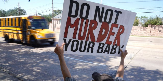 David Trujillo holds a sign as a school bus drives by on the street in front of a building housing an abortion provider in Dallas, Thursday, Oct. 7, 2021. (AP Photo/LM Otero)