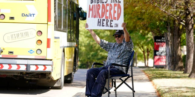 David Trujillo holds a sign as a bus travels by on the street in front of a building housing an abortion provider in Dallas, Thursday, Oct. 7, 2021. A federal judge ordered Texas to suspend a new law that has banned most abortions in the state since September. A federal appeals court reinstated the law late Friday.