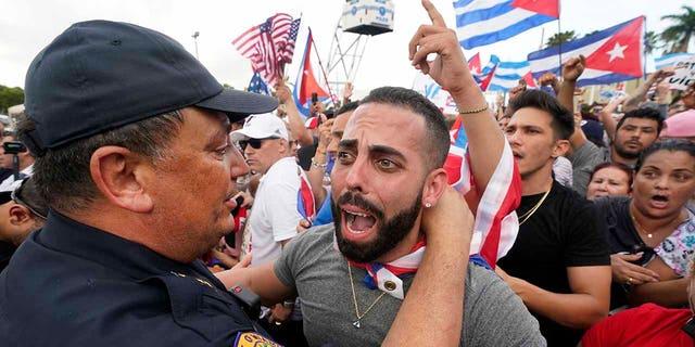 این چهارشنبه ، 14 ژوئیه 2021 ، در تصویر ، رئیس پلیس میامی ، آرت آسوودو ، در محله کوچک میامی در هاوانا ، تظاهرکنندگان را در آغوش می گیرد.