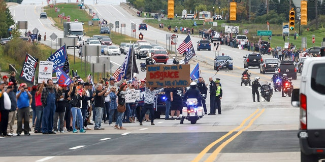 Anti-Biden demonstrators spill out into the street as they jeer the president's motorcade after a visit to the International Union of Operating Engineers Local 324 training facility in Howell, Michigan, Oct. 5, 2021.