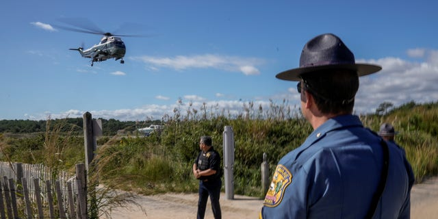 A Delaware State Trooper watches as Marine One carrying U.S. President Joe Biden takes off from Gordons Pond in Rehoboth Beach, Delaware, U.S., September 20, 2021. REUTERS/Ken Cedeno