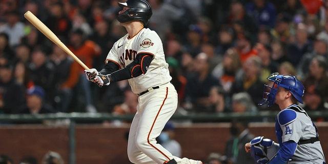 Buster Posey San Francisco Giants, kiri, menyaksikan home run dua kali di depan penangkap Los Angeles Dodgers Will Smith selama inning pertama Game 1 dari Seri Divisi Liga Nasional bisbol Jumat, 8 Oktober 2021, di San Francisco .  (Foto AP/John Hefti)