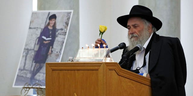 In this April 29, 2019, file file, Yisroel Goldstein, a rabbi of Chayad of Paulay, holds a yellow flower as he speaks at the funeral of Lori Kaye, pictured left, in Potow, California. Kaye, was killed on April 27, 2019, , had given Goldstein a flower as part of a flower the day before the shooting, which also injured Goldstein.  (AP Photo / Gregory Bull, Faira)
