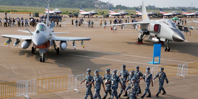 Chinese Air Force personnel march past the Chinese military's J10C fighter and JH-7A2 fighter bomber during 13th China International Aviation and Aerospace Exhibition, also known as Airshow China 2021, Wednesday, Sept. 29, 2021, in Zhuhai in southern China's Guangdong province. With record numbers of military flights near Taiwan over the last week, China has been stepping up its harassment of the island it claims as its own, showing an new intensity and sophistication as it asserts its territorial claims in the region. (AP Photo/Ng Han Guan)