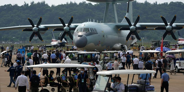 Visitors look at the Chinese military's KJ-500 airborne early warning and control aircraft during 13th China International Aviation and Aerospace Exhibition, also known as Airshow China 2021, on Wednesday, Sept. 29, 2021, in Zhuhai in southern China's Guangdong province. With record numbers of military flights near Taiwan over the last week, China has been stepping up its harassment of the island it claims as its own, showing an new intensity and sophistication as it asserts its territorial claims in the region. (AP Photo/Ng Han Guan