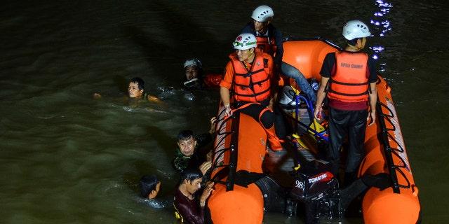 Los equipos de rescate buscan víctimas ahogadas en un río en Ciamis, Java Occidental, Indonesia, el viernes 15 de octubre de 2021.