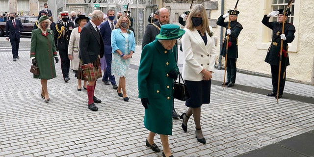 Britain's Queen Elizabeth II, center, arrives at the Scottish Parliament in Edinburgh, followed by Prince Charles and Camilla, Duchess of Cornwall, left, where she will deliver a speech in the debating chamber to mark the official start of the sixth session of Parliament, in Edingurgh, Scotland.