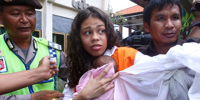 In this Tuesday, April 21, 2015, file photo, Heather Mack of Chicago, center, is escorted by police officers as he arrives in the courtroom for her sentencing hearing at a district court in Denpasar, Bali, Indonesia. (AP Photo/Firdia Lisnawati, File)