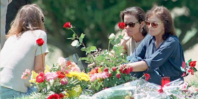 Murder victim Nicole Brown Simpson's mother Juditha (R), and sisters Denise (C) and Tanya (L) sit next to her grave surrounded by flowers, in Lake Forest, Calif.