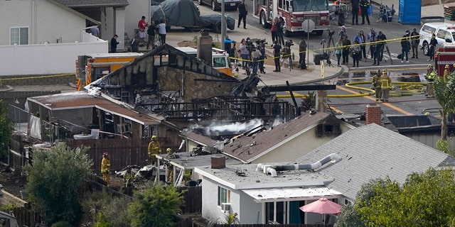 Emergency crews work a the scene of a small plane crash, Monday in Santee, Calif. (AP Photo/Gregory Bull)