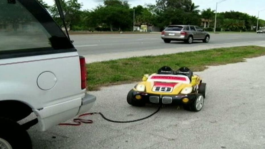 Risky ride: Couple tow granddaughter behind SUV in toy car