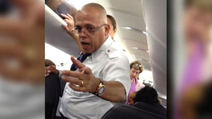 Airline employee confronts angry passengers on board plane after 5 hour delay