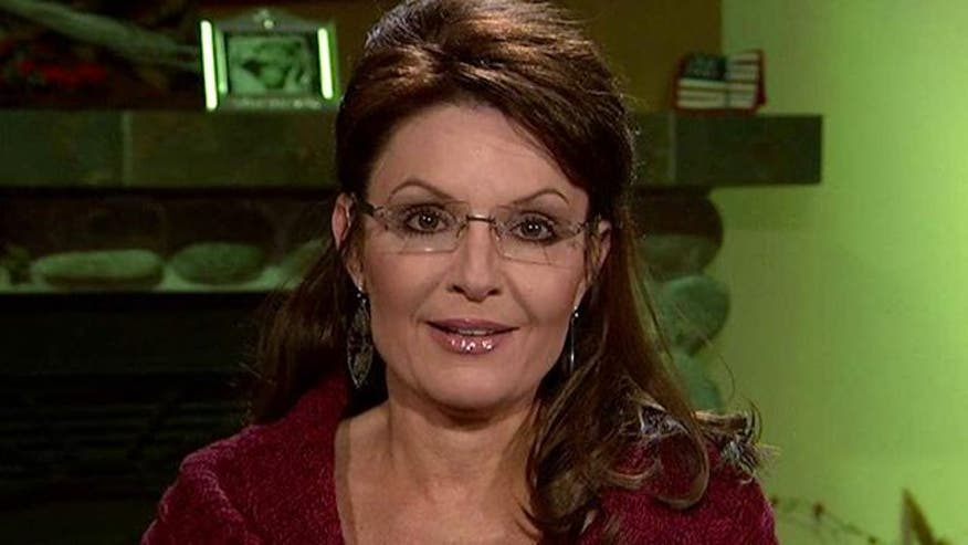 Former Alaska governor Sarah Palin reacts to protests