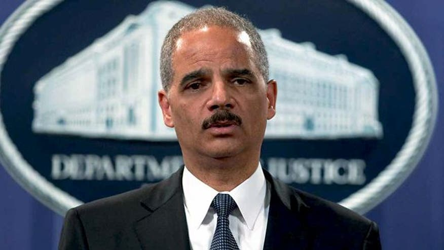 Attorney general suggests extremist critics target him and Pres. Obama because they're both African-American